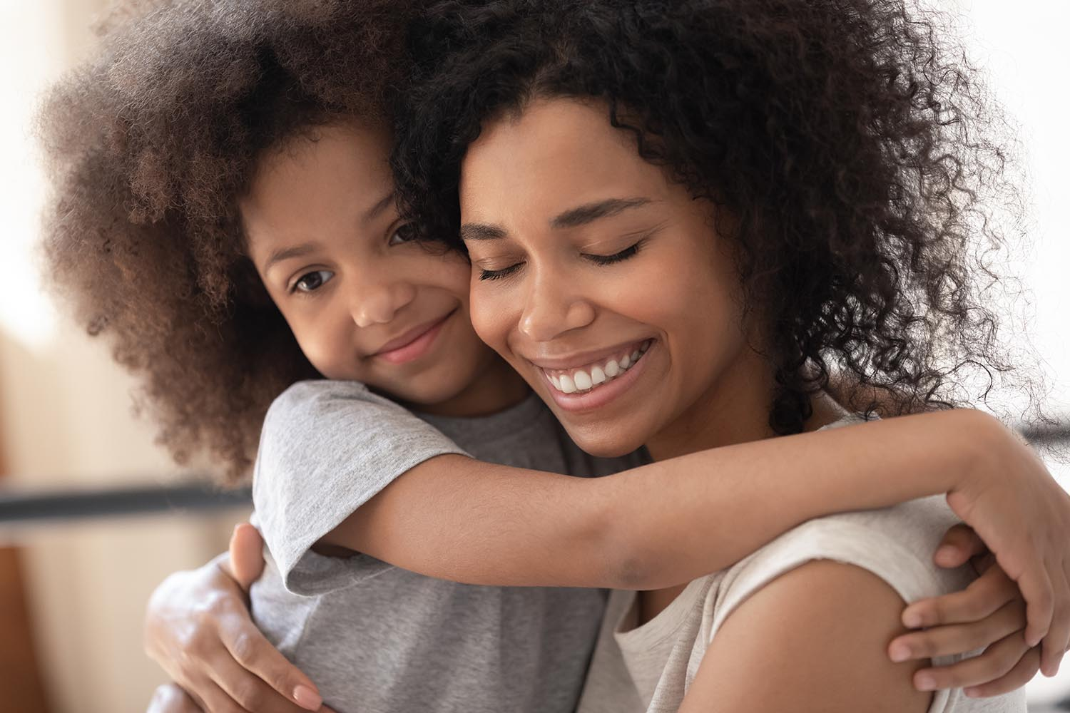 Close up beautiful faces happy family portrait loving african daughter hugs mother, mom enjoy moment of tenderness closed eyes feels deep love to her pretty kid, adoption protection offspring concept